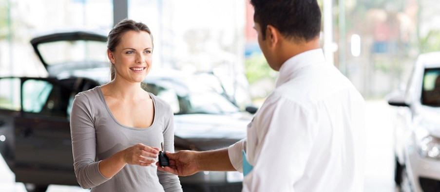 young woman receiving her new car key from salesman