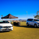 two white Mercedes-Benz vehicles parked on the grass in front of a pop-up tent
