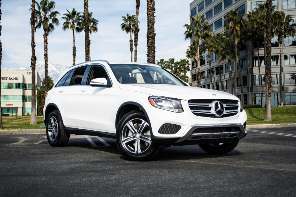 White Mercedes-Benz GLC parked by palm trees