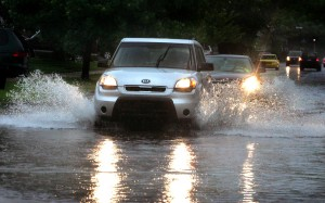 A driver tries to motor a Kia SUV through the water on Richmond Street in Southgate on Wednesday. In Melvindale, city officials said 3.75 inches of rain fell in 12 hours. (Larry Caruso/Photo Edi-tor)