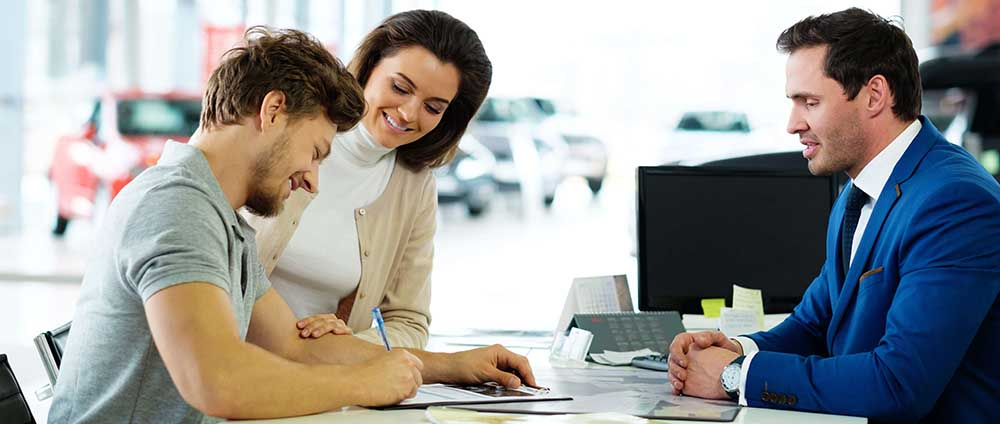 Young couple signing car buying documents