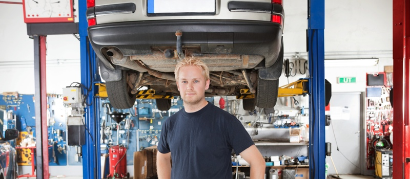 Portrait of smiling young mechanic standing inside his auto repair shop