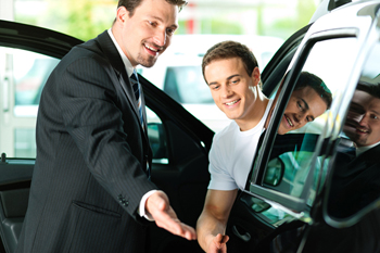 car salesman showing car