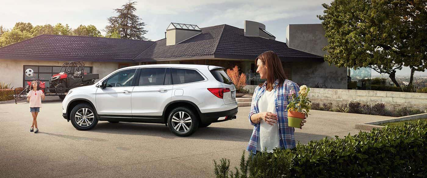 Honda Pilot parked outside a house with the family
